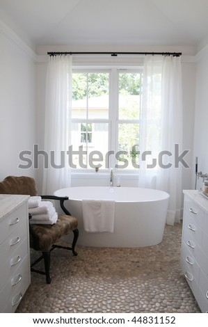 A beautiful white bathroom with stone floor