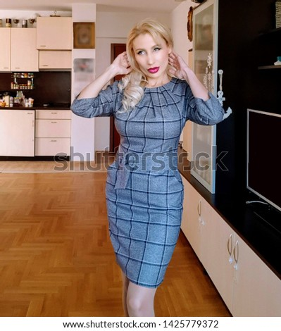 A beautiful white blonde woman with long wavy hair and light green eyes, purple  lipstick in a slim gray stylish checked dress with a wide textile belt