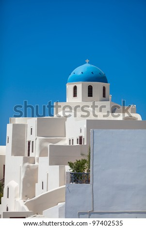 A beautiful white church with blue dome against blue sky in Oia, Santorini island, Greece