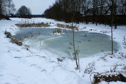 A beautiful white frozen pond covered in ice and snow in the winter time.