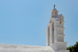 A beautiful white painted chapel on the peaceful Greek island of Folegandros.A view of the bell tower and the curved roof. Classical cycladic architecture. The building is lit by the evening sunshine.