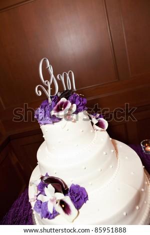 A beautiful white wedding cake with purple flowers