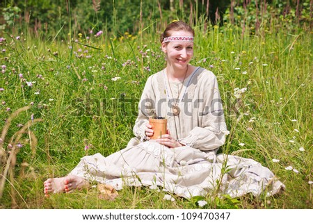 A beautiful white woman wearing a Russian national dress sitting on a meadow, and holding a birch bark basket with a black currant.