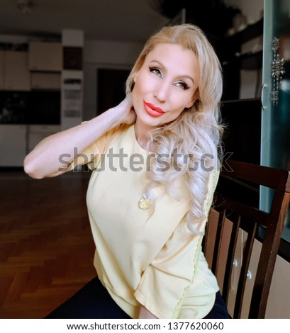 Stock Photo A beautiful white woman with wavy blonde long hair and light green eyes, pink coral lips and yellow silk top with embroidery decoration on the sleeves and black leather leggings