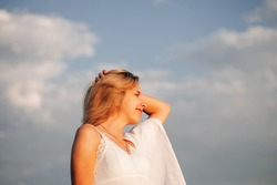 A beautiful woman against the background of clouds in profile. Romantic photo of a young happy smiling woman.