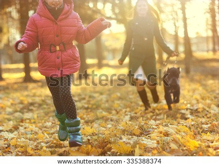 A beautiful woman and daughter and his dog Cane corso posing outside in autumn park. Concept blur #335388374