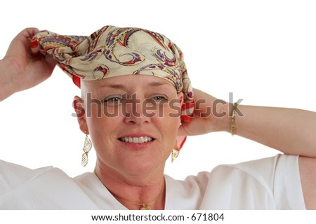 A beautiful woman, bald from chemotherapy,  prepares to remove the scarf covering her head.  Second in a sequence.