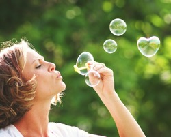 a beautiful woman blowing bubbles (one in the shape of a heart)