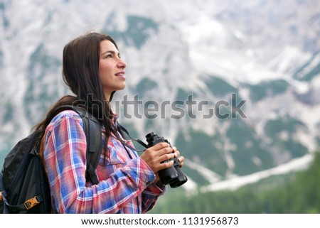 A beautiful woman camping, explore the nature around her with binoculars, to look for animals or paths to go. Concept of: curiosity, research, exploration, campsites for children.