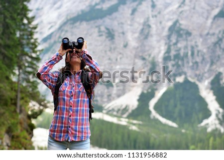 A beautiful woman camping, explore the nature around her with binoculars, to look for animals or paths to go. Concept of: curiosity, research, exploration, trekking