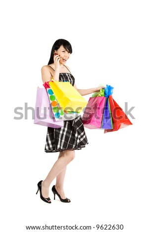 A beautiful woman carrying shopping bags while talking on the phone