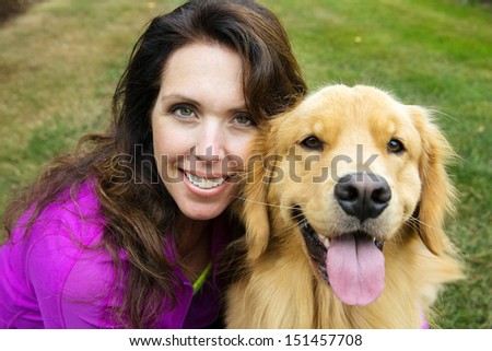 A beautiful woman close to her handsome golden retriever dog