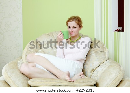 A beautiful woman drinking tea in the armchair