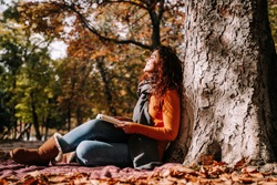 A beautiful woman enjoying the sun in a park in an autumnal day. She is sitting and leaning against a tree while having a book on her legs. Lifestyle autumnal outdoors