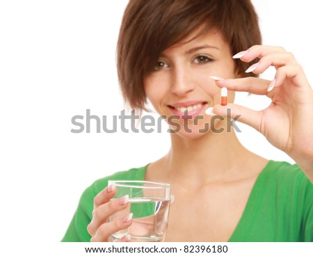 A beautiful woman holding a pill and water, isolated on white