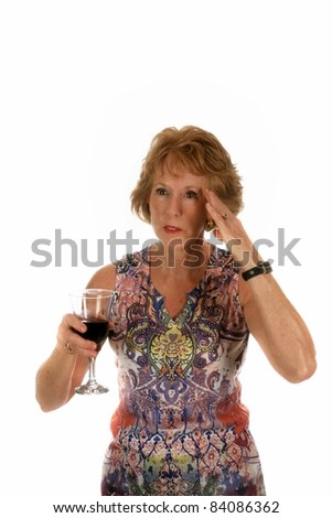 a beautiful woman holds a glass of red wine and holds her hand to her head because she has a headache. isolated on white with room for your text.