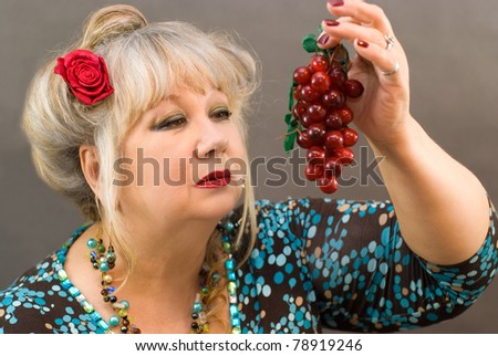 A beautiful woman holds a red grape