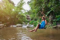 A beautiful woman in a blue dress is happy to sit on a swing over a waterfall in the background of green trees and sunlight.