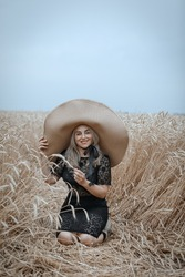 a beautiful woman in a wide-brimmed straw hat is resting in a wheat field