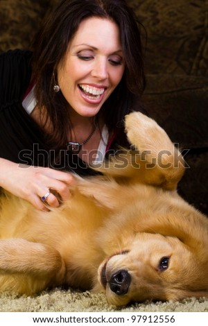 A beautiful woman in her early 40s spending time with a very handsome Golden Retriever Dog at home.