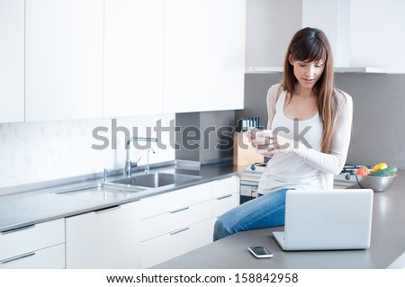 A beautiful woman in her kitchen during her breakfast. She is using her laptop.