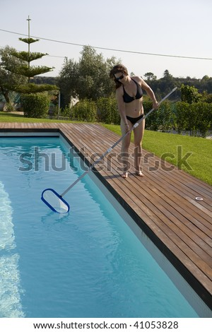 a beautiful woman is cleaning the swiming pool