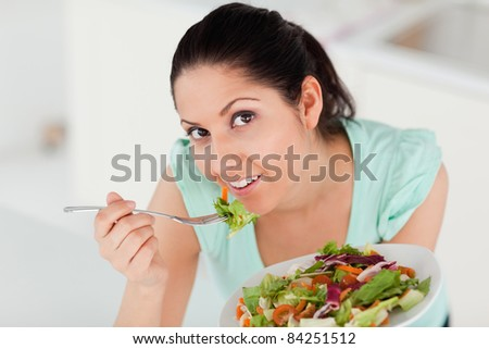 A beautiful woman is eating a salad