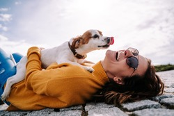 A beautiful woman laughing while her pet is licking her face in a sunny day in the park in Madrid. The dog is on its owner between her hands. Family dog outdoor lifestyle