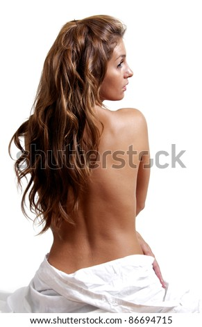A beautiful woman sits with her bare back towards the camera, her face in profile.