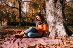 A beautiful woman sitting and leaning against a tree while reading a book in a park in a sunny autumnal day. Lifestyle autumnal outdoors.