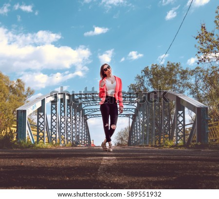 A beautiful woman stand in front of an old bridge in Gyor, Hungary. The lights are smooth, and the focus is on the girl. Stock fotó ©