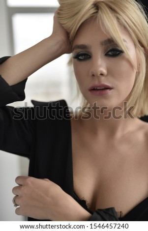A beautiful woman stands near the wall. Sexy girl, sexy look