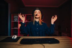 A beautiful woman streamer in a headset is sitting at the computer after a game and wants to calm down by meditating. Woman gamer meditating in bedroom at home with red light.