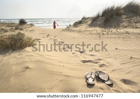 A beautiful woman walks barefoot through sand dunes towards to sea leaving her flip flops behind