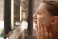 A beautiful woman washes her skin on her face in the bathroom by the mirror. side view . Healthy facial skin. Skin care. Pore cleansing.