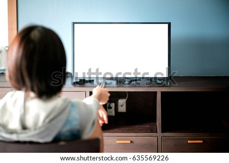 A Beautiful woman watching TV sitting on couch at home , watching TV on couch at home in the living room