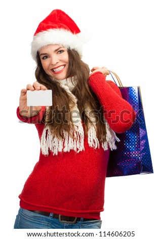 A beautiful woman wearing a Christmas hat and holding shopping bags and a blank business card. Isolated on white.