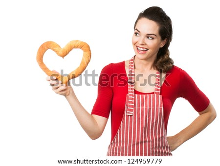 A beautiful woman wearing an apron smiling and holding and looking at a love heart made out of bread. Isolated on white.