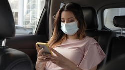 A beautiful woman with a mask to prevent the virus using her cell phone in a car, a passenger wearing a mask and checking her cell phone, on a trip through the city