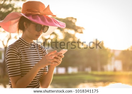 A beautiful woman with pink hat and black eyeglasses has playing phone in the evening with sunset time at garden park and river. #1018341175