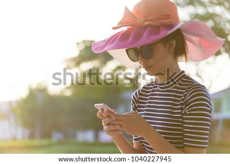 A beautiful woman with pink hat and black eyeglasses has playing phone in the evening with sunset time at garden park and river. #1040227945