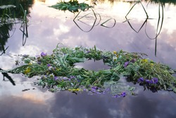 A beautiful wreath of wildflowers of summer flowers on dark water with the reflection of the sky floats. Midsummer festival, wreath for the goddess Lada. Accessory for the holiday of Ivan Kupala.