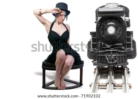 A beautiful young actress dancer wearing a top hat sitting beside a train