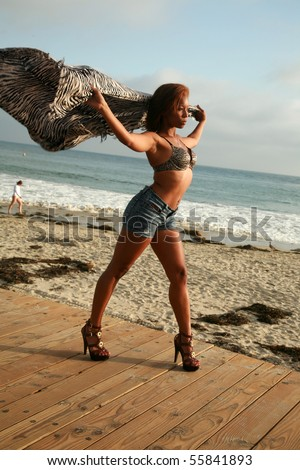 a beautiful young african american woman holds her shawl into the wind as if she can fly