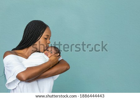 A beautiful young African-American woman with braids is kissing her newborn son and looking at him with love on a teal blue background.
