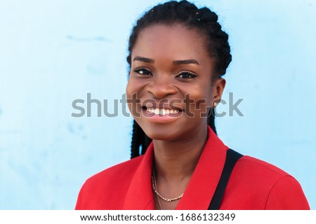a beautiful young african american woman with pigtails hairstyle in a red business suit on a blue background