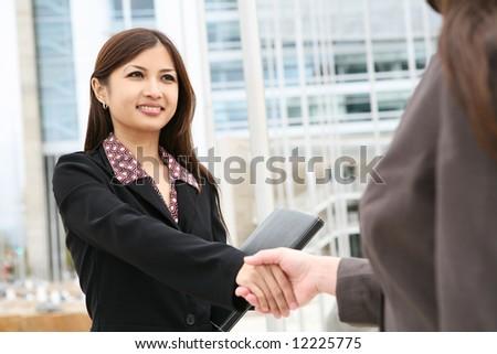 A beautiful young asian business woman shaking hands