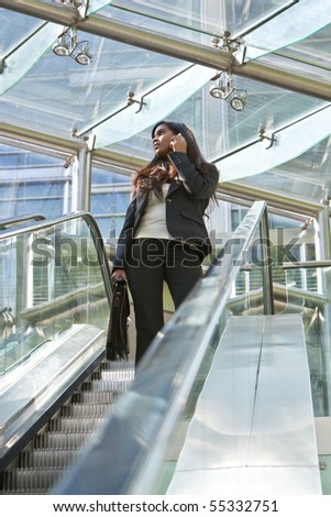 A beautiful young Asian businesswoman using her cell phone while traveling on an escalator in a modern hi tech office building