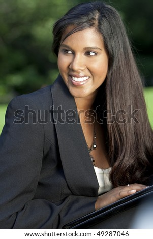 A beautiful young Asian businesswoman with a folder and a wonderful smile shot outside in golden sunshine - stock photo