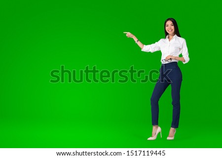 Photo of  A beautiful young asian woman, anchor or tv presenter is getting filmed inside a green screen chroma key studio to create a video with removable background that can be replaced